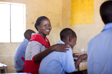Female teacher with studentsin classroom. Kenya, Africa.