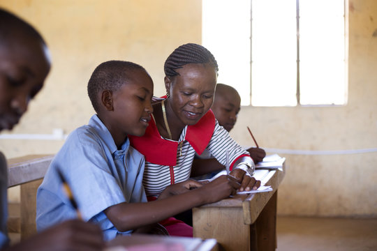 Teacher with students in classroon. Kenya, Africa.
