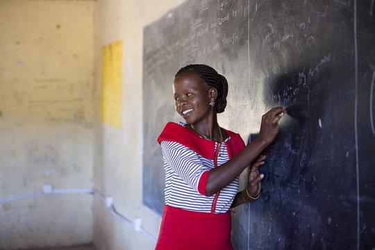 Female teacher in classroom. Kenya, Africa.
