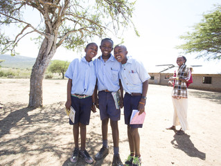 Smiling school boys with female teacher outdoors. Kenya, Africa.