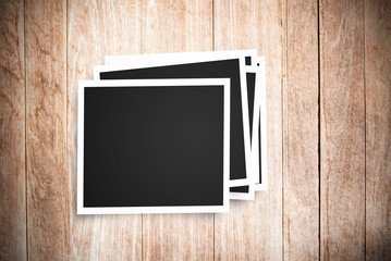 Blank photo frame on brown wood background.