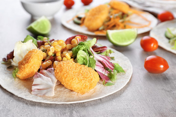 Delicious fish taco with filling on table, close up