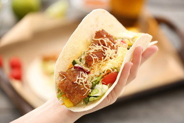 Hand with delicious fish taco on blurred background