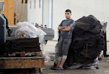 A worker looks on near leather in the factory of Al Rowad Leather Tannery at El Robbiki Leather City in Badr City
