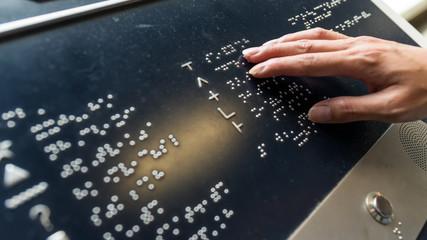 Hand touching on Braille alphabet