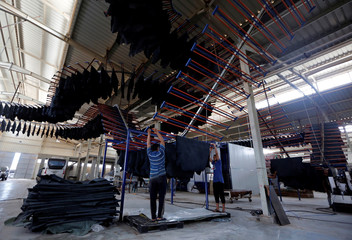 Workers carry leather in the factory of Al Rowad Leather Tannery at El Robbiki Leather City in Badr City, east of Cairo