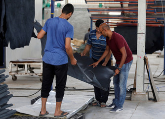 Ahmed El Gabbas, Managing Director of Al Rowad Leather Tannery speaks with workers in the factory at El Robbiki Leather City in Badr City