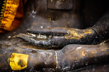 Hands of Golden Buddha statue in the  buddhist temple, in public area.