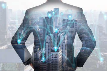 Double exposure of A back turned businessman, city and urban in the foggy morning with pin node networking as business, vision of leader, technology, communication and innovation concept.