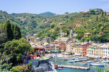 Beautiful aerial daylight view from top to ships on water and buildings in Portofino city of Italy. Tourists walking on sidewalk. Top view