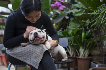 Young Asian Woman Holding her Dog in the Garden