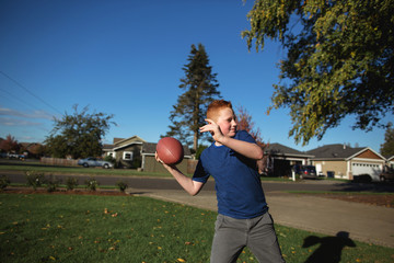 Fun family - dad and sons - playing football in front yard toget