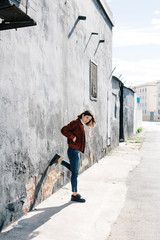 Woman leaning wit one foot on wall