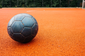 old and blue football without any logos on orange ground
