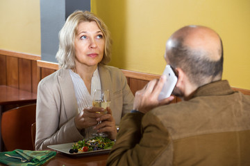 elderly woman bored in a restaurant while her man talking on the phone
