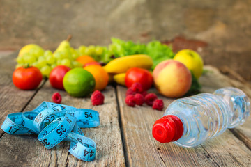 Fruits, vegetables, measure tape, water on wooden background.