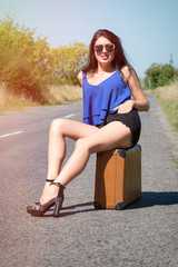 Happy beautiful girl traveler with a suitcase on the road, hitchhiking. The concept of travel, adventure, vacation, freedom.