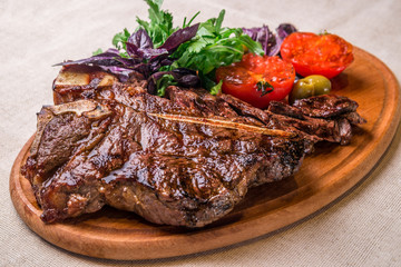 Tuinposter Steakhouse Appetizing steak on the bone, with tomatoes and herbs, on a wooden board. Horizontal frame