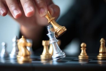 Hand of business woman moving golden chess to defeat and kill silver king chess on white and black chess board for business challenge competition winner and loser concept shallow depth of field