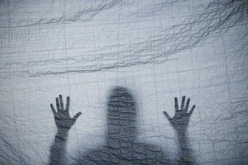 Shadow of a man behind a curtair