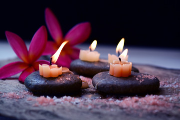 Soft Light and candles scented with refreshing fragrance and salt scrub on black stones, including plumeria flower, spa concept, Thai massage on black back ground.