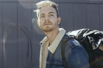 Portrait of Man in Shearling Lined Denim Jacket Carrying Leather Backpack