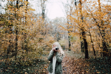 Blonde woman taking picture during autumn