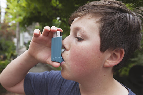 A young boy using his Asthma medication