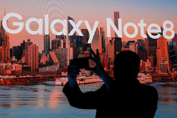 A man takes a picture with a smartphone at Samsung Electronics' Mobile Communications launch event for the Galaxy Note 8 smartphone in New York City
