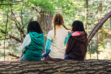Three mixed race girls sitting on a log in a forest