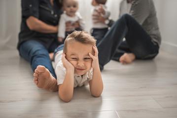 A Boy Makes A Funny Face Next to His Family