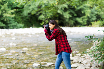 Female model in plaid shirt taking a photo with a camera near the river