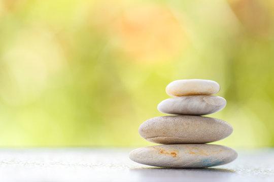 Stones pyramid symbolizing stability, zen ,Zen spa concept , Zen Massage Stone against green bokeh background