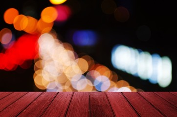 empty wooden floor or terrace with abstract night light bokeh, blurred view of street traffic light in the city at night, copy space for display of product or object presentation, vintage color tone