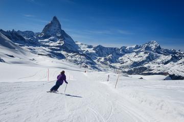 Female skier skiing on the slopes of Matterhorn mountain