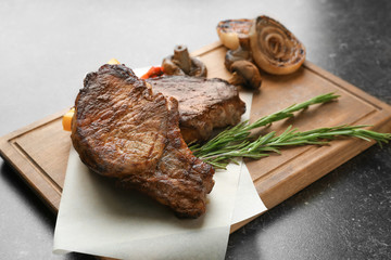 Tasty grilled steak with vegetables on wooden board