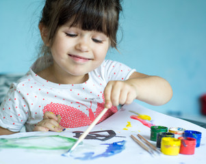 Lovely little child, brunette toddler girl using her imagination is painting while sitting at table