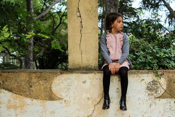 Little girl sitting on balcony and looking away