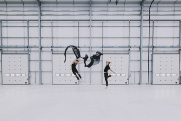 Two men leaping in the air, dancing with black silk fabric in an empty warehouse