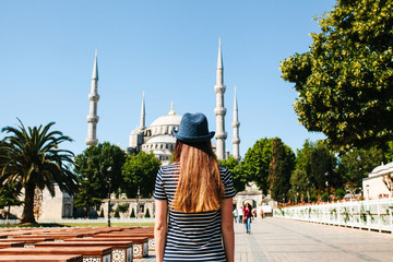 A young girl traveler in a hat from the back in Sultanahmet Square next to the famous mosque called the Blue Mosque in Istanbul, Turkey. Travel, tourism, sightseeing.