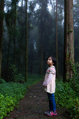 Cute little girl standing alone in the forest