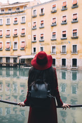 Woman with red hat standing in front od a beautiful building in Venice