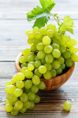 Juicy white grapes in a wooden bowl.