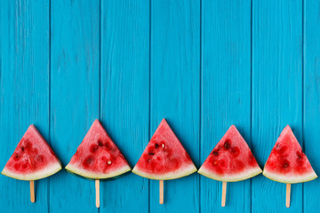 Watermelon slice popslices on a blue wooden background, free space for advertisement or text. Organic fresh tasty fruits