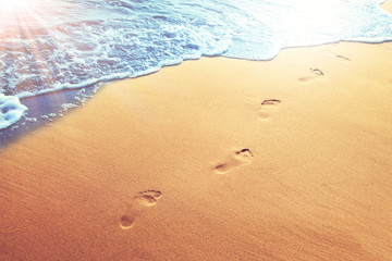 Fußspuren im Sand am Strand Fototapete