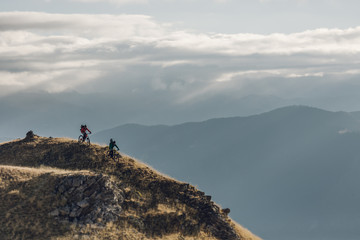 A couple of mountain bikers at the summit of a scenic mountain start downhill at the sunrise
