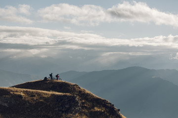 A couple of mountain bikers at the summit of a scenic mountain enjoying the view at the sunrise