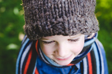 Closeup of young boy in knitted hat and striped scarf