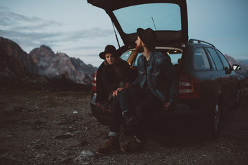 Hipster couple sitting in a trunk of their car on top of the mountain.