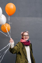 Teen girl holding orange and white balloons,